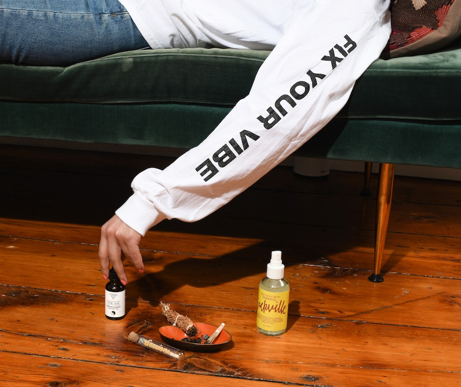 woman reaching for OG-tonic cbd with pre-roll and room-spray on the floor
