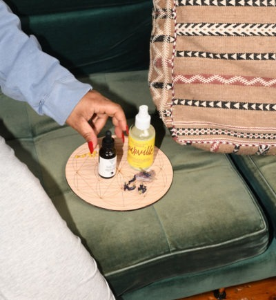 woman reaching out to grab powerful room-spray sackville-and-co with og-tonic on green couch
