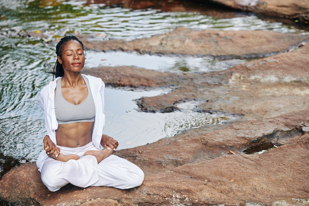 woman sitting on rocks in a stream meditating legs crossed eyes closed