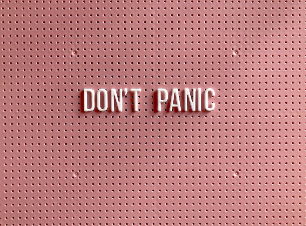dont-panic pink background white letters bulletin board